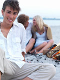 Happy young guy with couple in the background Stock Photo