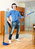 Happy young  guy  with dustpan and brush Stock Photography