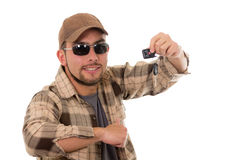 Happy young guy in flannel shirt and cap showing. Car keys in his hand isolated on white Stock Images
