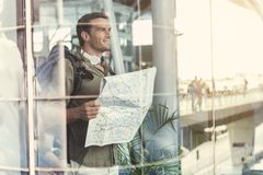 Cheerful man is enjoying view. Happy young guy with headphones and backpack is holding map and looking out through window glass dreamily. He is standing at Stock Photography