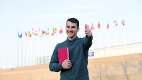 International exchange experience. Happy young guy holding books to chest standing outdoors over different countries flags background showing thumb up gesture stock video footage