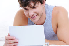 Happy young guy with laptop Stock Photography