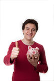 Happy young guy with piggy bank Royalty Free Stock Photo