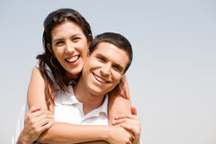 Happy young guy piggybacking his girlfriend Royalty Free Stock Photo