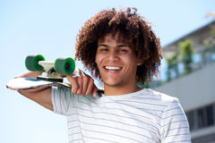 Happy young guy smiling outside with skateboard Stock Image