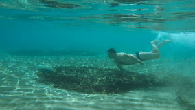 Happy young guy swims underwater stock video footage