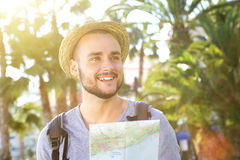 Happy young guy on vacation holding map Stock Photography