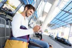 Happy young guy waiting for transport Royalty Free Stock Photography