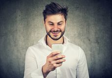 Happy young guy watching smartphone royalty free stock photo