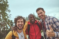 Happy young guys are hugging each other stock image