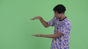 Happy young handsome African man snapping fingers and showing something. Studio shot of young handsome African man with dreadlocks against chroma key with green stock video footage