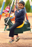 Happy young handsome boy(kid) playing on swing sets in a park Stock Images