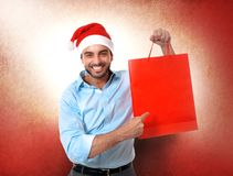 Happy young handsome man wearing santa hat holding red shopping. Happy young attractive man wearing Santa hat holding and pointing red shopping bag in Christmas Stock Image