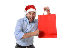 Happy young handsome man wearing santa hat holding red shopping bag. Happy young attractive man wearing santa hat holding and pointing red shopping bag in Royalty Free Stock Images