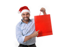 Happy young handsome man wearing santa hat holding red shopping bag. Happy young attractive man wearing santa hat holding and pointing red shopping bag in Royalty Free Stock Photos
