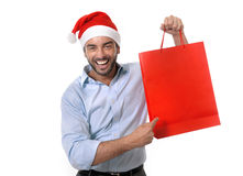 Happy young handsome man wearing santa hat holding red shopping bag. Happy young attractive man wearing santa hat holding and pointing red shopping bag in Royalty Free Stock Photography