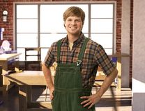 Happy young handyman in workshop Royalty Free Stock Photos