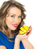 Happy Young Healthy Woman Holding a Fresh Ripe Juicy Mango Half Stock Images