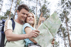 Happy young hiking couple holding map with woman pointing away in forest Royalty Free Stock Image