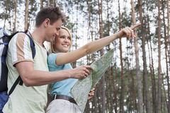 Happy young hiking couple holding map with woman pointing away in forest Stock Image