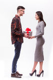 Happy young hipster couple with present isolated on a white background. stock photography