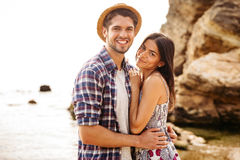 Happy young hipster couple standing at the beach and hugging Royalty Free Stock Images