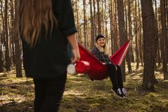Happy young hipster girl enjoys life and nature on hammock with other woman in the summer forest. royalty free stock images