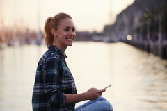 Happy young hipster girl looking away while sitting with mobile phone in beautiful summer evening near sea port, Royalty Free Stock Photos