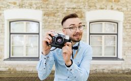 Happy young hipster man with film camera in city Stock Photography