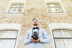 Happy young hipster man with film camera in city Royalty Free Stock Images