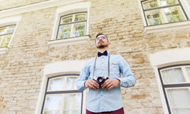 Happy young hipster man with film camera in city Stock Photo