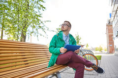 Happy young hipster man with tablet pc and bike Stock Photos