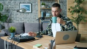 Happy hipster talking in microphone and drinking tea in sound recording studio. Happy young hipster is talking in microphone and drinking tea in sound recording stock video footage