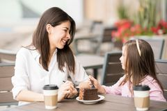 Hispanic brunette talking with a little girl in a cafe. Happy young hispanic brunette talking with a little girl in a restaurant Royalty Free Stock Images