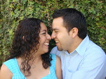 Happy, young Hispanic Couple in love. They are smiling and squishing their noses together Royalty Free Stock Images