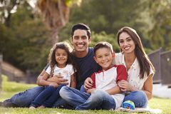 Free Happy Young Hispanic Family Sitting The On Grass In The Park Smiling To Camera, Close Up Stock Photography - 144582982
