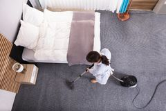 Housekeeper Cleaning Carpet With Vacuum Cleaner. Happy Young Housekeeper Cleaning Carpet With Vacuum Cleaner In Hotel Room royalty free stock images