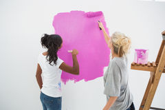 Happy young housemates painting wall pink Royalty Free Stock Images