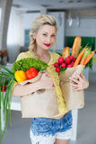 Happy young housewife with bags full of vegetables Stock Photography