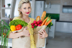 Happy young housewife with bags full of vegetables Royalty Free Stock Photo