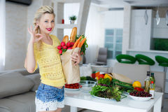 Happy young housewife with bags full of vegetables Stock Images