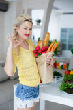 Happy young housewife with bags full of vegetables Royalty Free Stock Photography