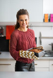 Happy young housewife with baking dish with bread Stock Photography