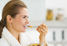 Happy young housewife in bathrobe having healthy breakfast Stock Photography