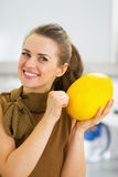 Happy young housewife checking ripeness of melon Royalty Free Stock Photo