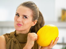 Happy young housewife checking ripeness of melon Royalty Free Stock Images