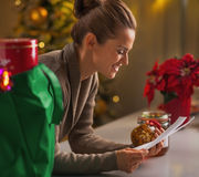 Happy young housewife with checks exploring christmas purchases Royalty Free Stock Image