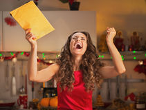 Happy young housewife with christmas package rejoicing Royalty Free Stock Image