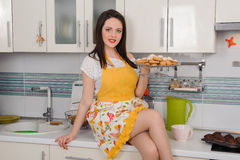 Happy young housewife with cookies in kitchen Stock Photos