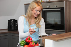 Happy young housewife cooking dinner Royalty Free Stock Photos
